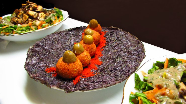 Raw wallnut balls served on a purple nori sheet with lettuce and marinated mushrooms